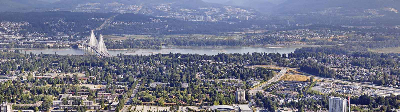 Aerial photograph overlooking the Port Mann bridge and the Fraser River with Surrey in the foreground.