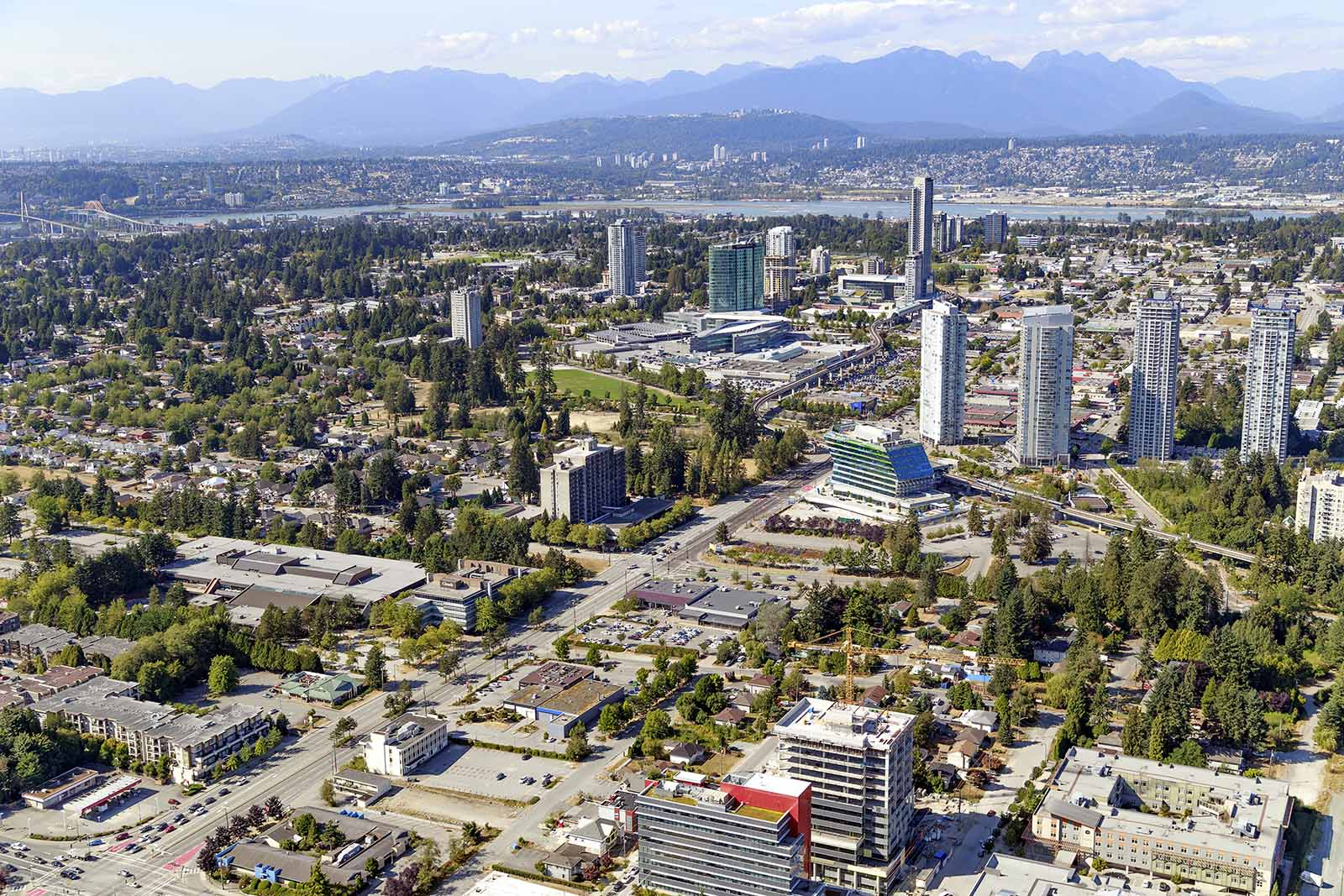 Aerial image of Surrey City Centre, including office towers, residential high-rises, and low-rise commercial/retail centres.